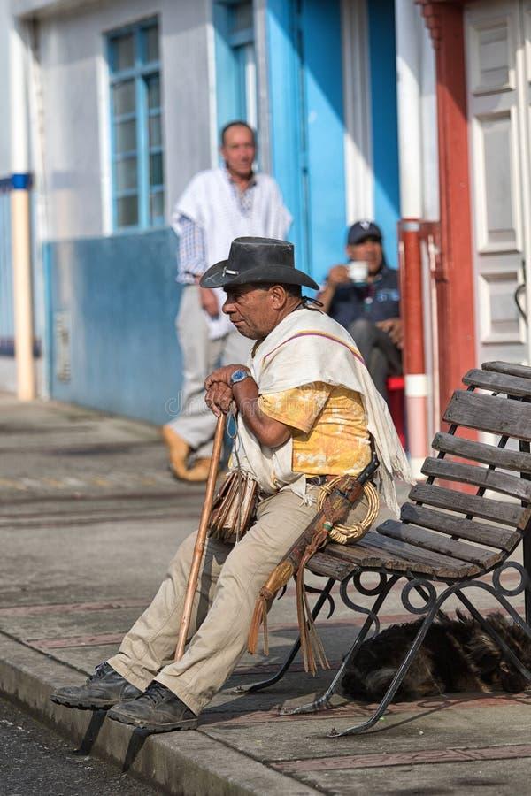 Granjero que se sienta en un banco en Salento Colombia fotos de archivo
