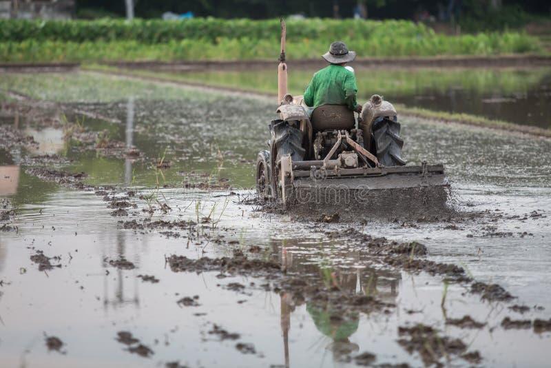 Granjero que se sienta en un tractor fotos de archivo
