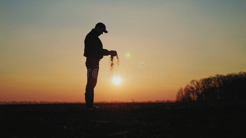 Granjero que sostiene el suelo en manos en el campo fotografía de archivo