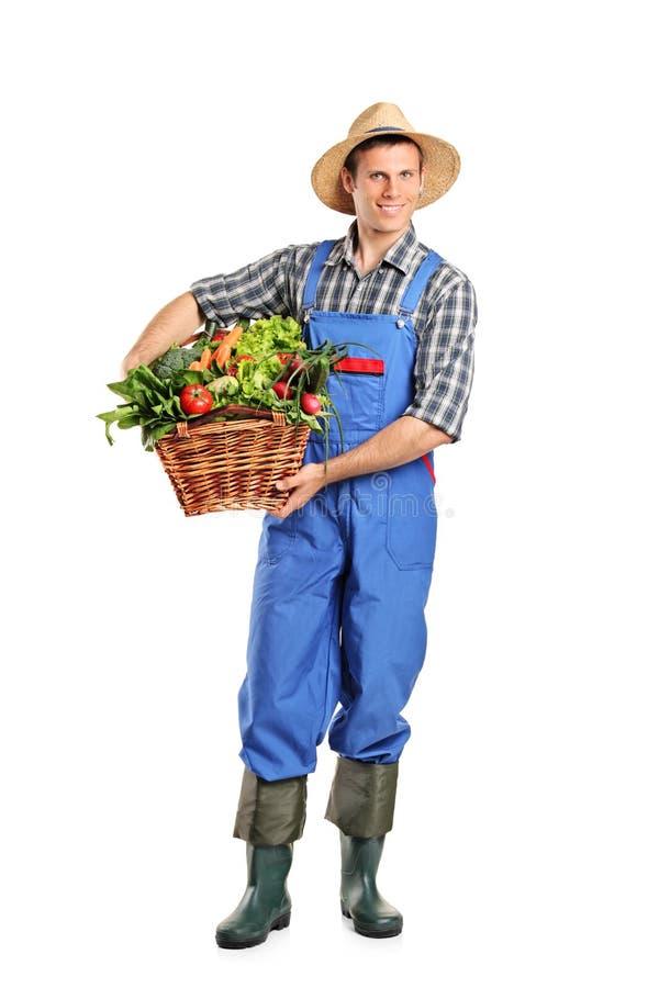 Granjero que sostiene una cesta llena de vehículos foto de archivo libre de regalías