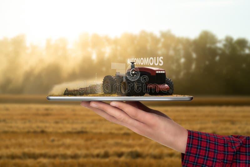 Granjero que sostiene una tableta con el tractor autónomo imágenes de archivo libres de regalías