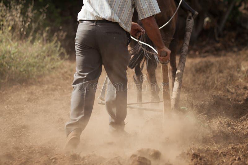 Granjero y caballo que aran el campo del granjero imagenes de archivo