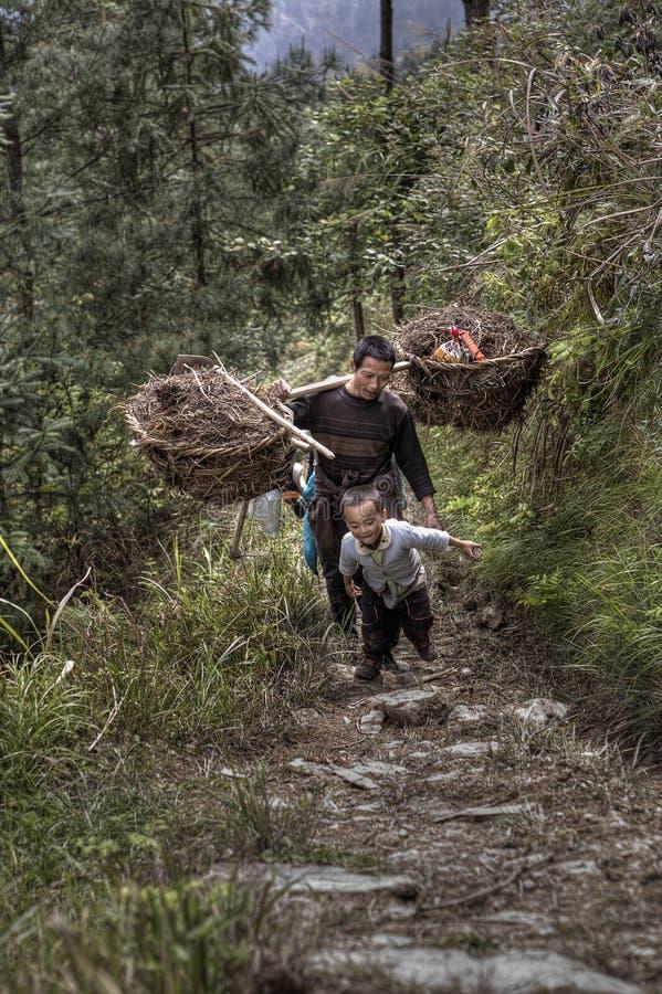 Granjeros del padre y del hijo que vuelven del trabajo en el terreno, China rural imagenes de archivo