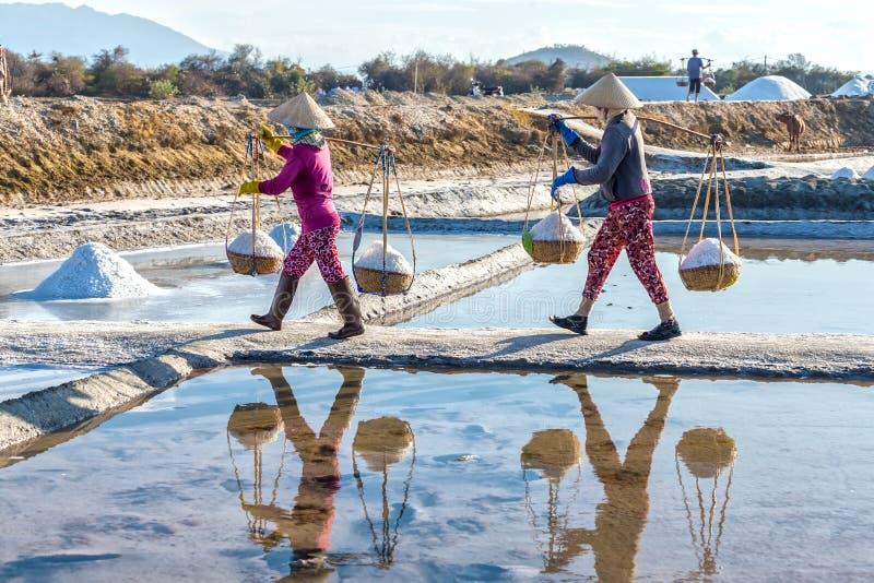 Granjeros que llevan la sal en el terraplén fotografía de archivo