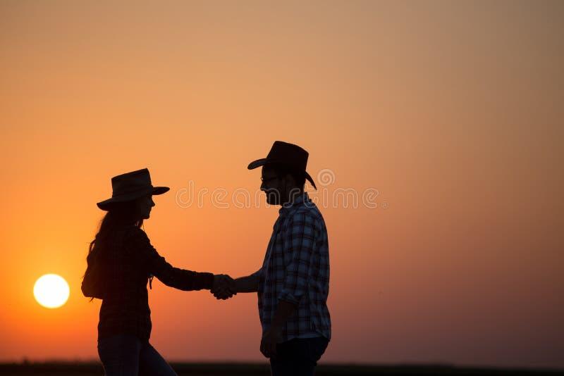 Granjeros que sacuden las manos en la puesta del sol fotografía de archivo