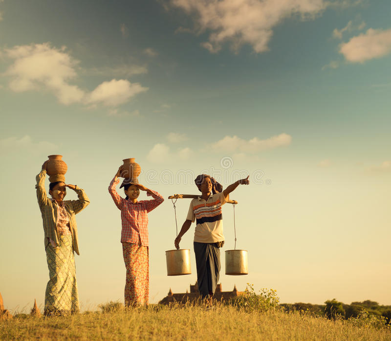 Granjeros tradicionales birmanos asiáticos del grupo en puesta del sol imagen de archivo