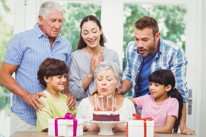 Granny blowing birthday candles with family stock photos