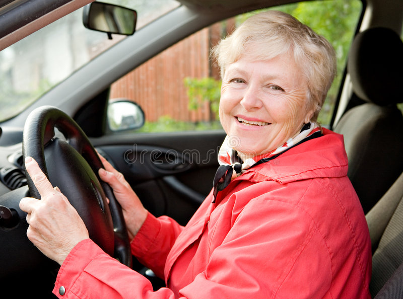 Granny in a car. The smiling elderly woman in a red jacket at the wheel the car