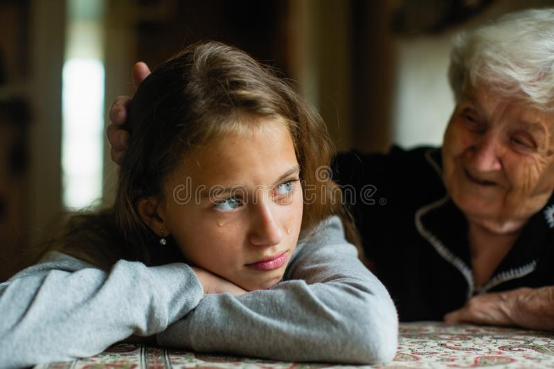 Granny comforting a crying little girls-granddaughter. Help. Granny comforting a crying little girls-granddaughter stock photography