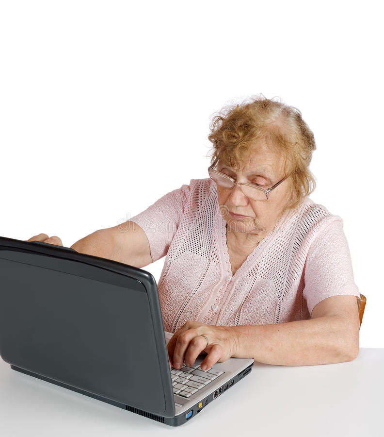 Granny in glasses looks at the notebook royalty free stock image