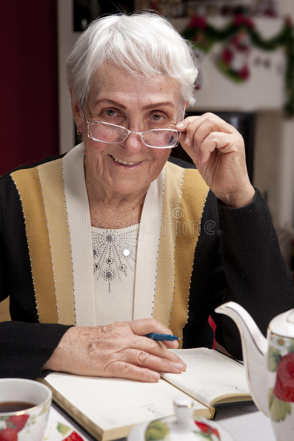 Granny in glasses writes a letter stock photo