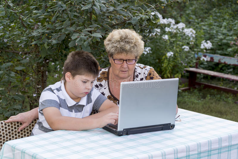 Granny with a grandson behind the laptop outdoors royalty free stock photo