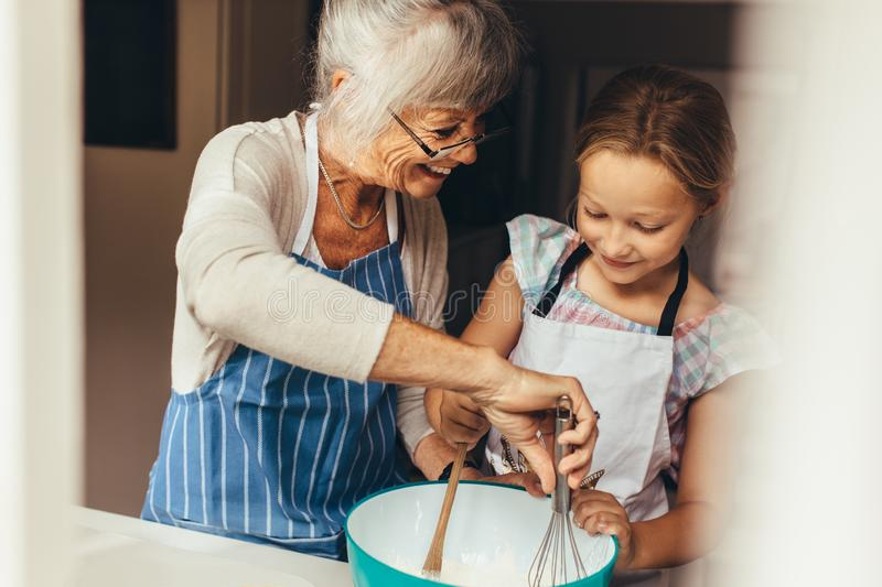 Granny and kid cooking in kitchen royalty free stock images