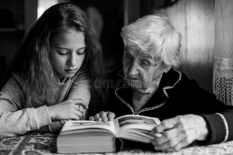 Granny with a little granddaughter reading a book. Help. Granny with a little granddaughter reading a book royalty free stock photography