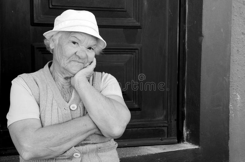 Granny Looking to Camera with Happy Naughty Expression. Granny, sitting on doorstep, looking to camera with happy naughty facial expression. Black and white