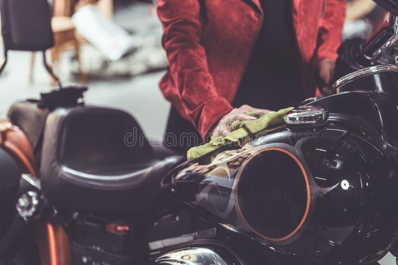 Granny rubbing bike in mechanic shop royalty free stock photography