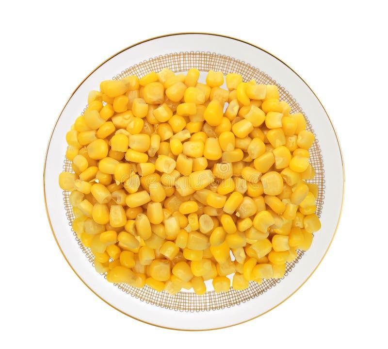 Grano amarillo dulce del maíz en la placa aislada en blanco fotos de archivo