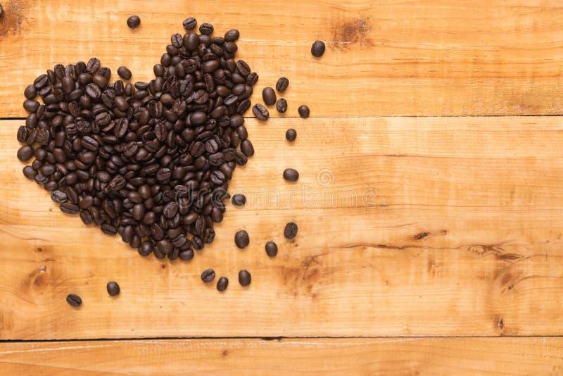 Grano de café en la forma de corazones en de madera del fondo marrón fotos de archivo