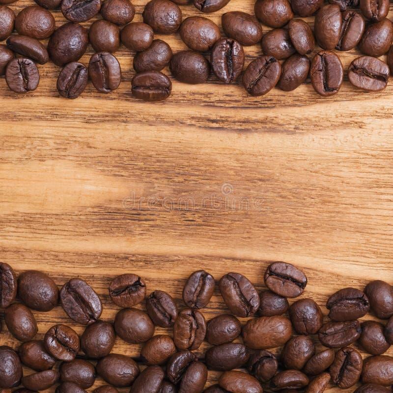 Grano de caf? El fondo de los granos de café asados es marrón en los tableros de madera disposici?n Endecha plana fotografía de archivo