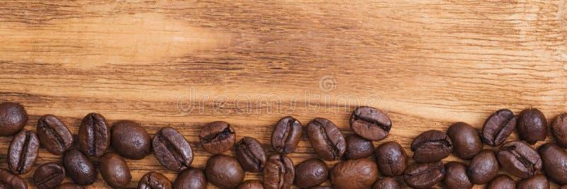 Grano de caf? El fondo de los granos de café asados es marrón en los tableros de madera disposici?n Endecha plana imagenes de archivo