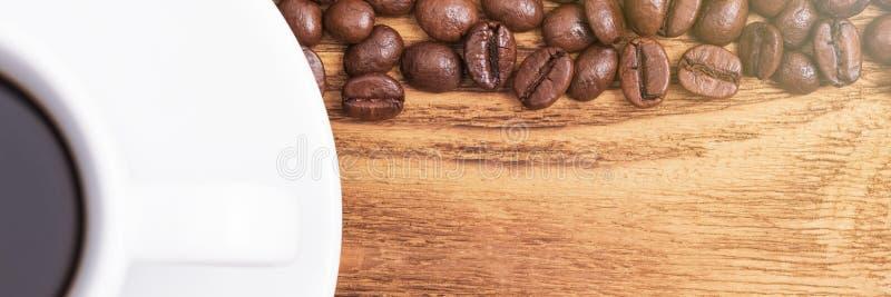 Grano de caf? En el fondo de tableros de madera a la taza de café y de granos de café dispersados disposici?n Endecha plana imagen de archivo