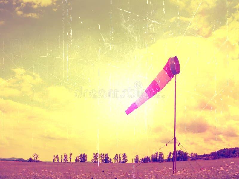 Grano del film Il giorno caldo dell'estate sull'aeroporto di sport con il windsock abbandonato, vento sta soffiando ed il windsoc fotografia stock libera da diritti