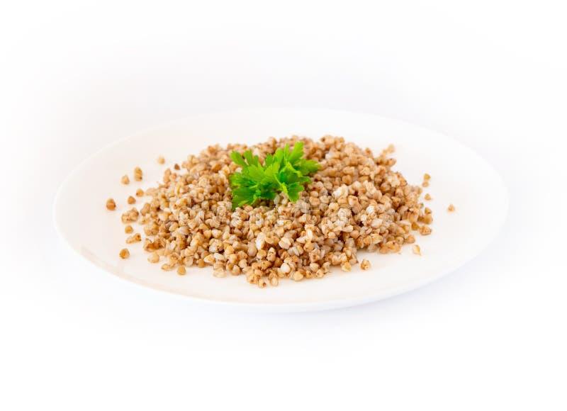 Grano saraceno con prezzemolo su un piatto su un fondo bianco fotografia stock