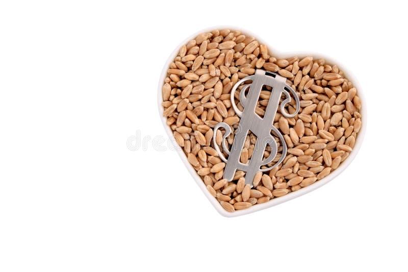 Grano, soldi ed amore Il simbolo del metallo delle bugie del dollaro americano in un piatto in forma di cuore riempito di grano C immagini stock