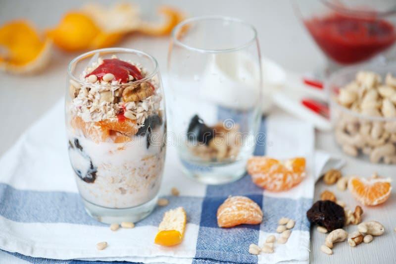 Granola βρωμών γιαουρτιού με τα μούρα, το μανταρίνι και τα καρύδια στα βάζα γυαλιού στοκ εικόνα