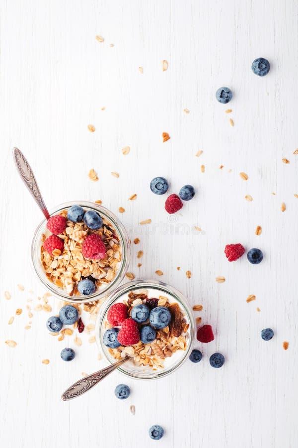 Granola με τα μούρα και γιαούρτι στα βάζα στοκ εικόνες