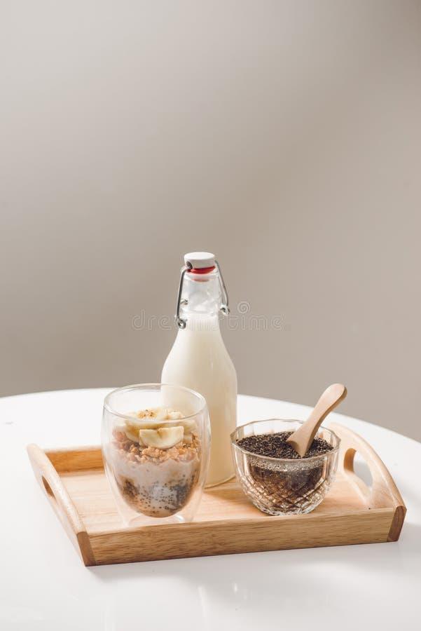 granola с миндалинами, семенами chia, бананом и киви и ягодами и опарником с молоком рядом стоковые фотографии rf