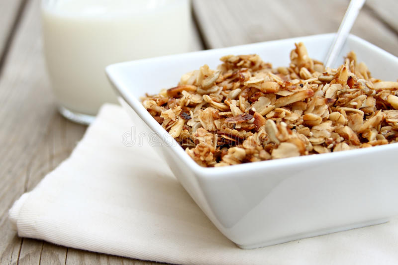 Granola. Bowl of granola with glass of milk royalty free stock photos