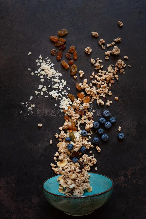 Granola, almonds, raisins and blueberries - the ingredients for a healthy breakfast. Close-up, top view on  dark background stock image