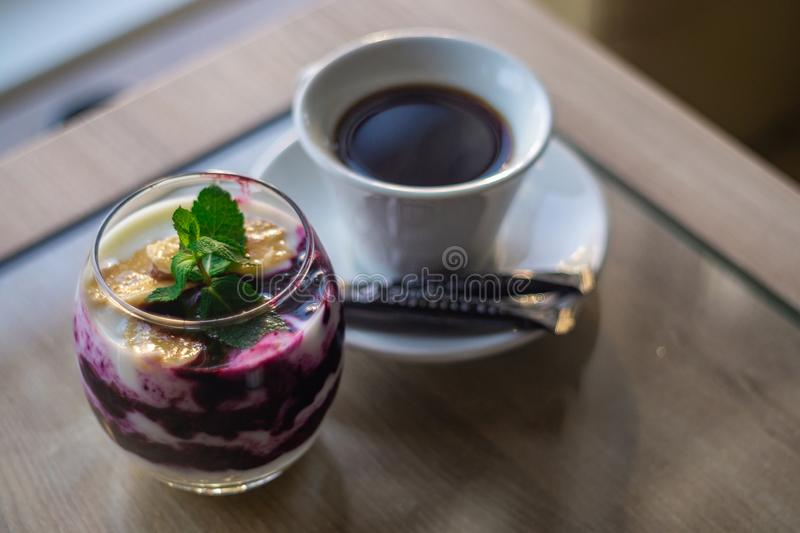 Granola avec la confiture de yaourt et de mûre avec la feuille en bon état sur le dessus et la tasse de café Fond brouillé Nourri images stock