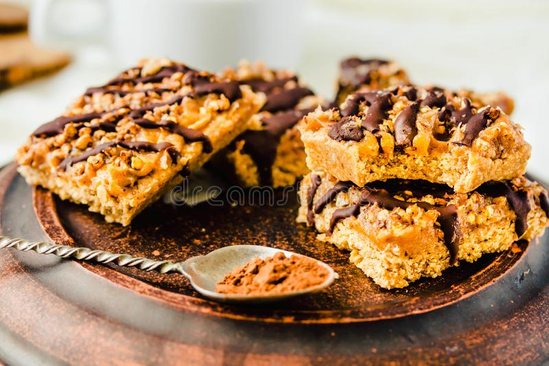 Granola bar cake with date caramel and chocolate. Healthy sweet dessert snack. Cereal granola bar with nuts, fruit and berries on royalty free stock photo