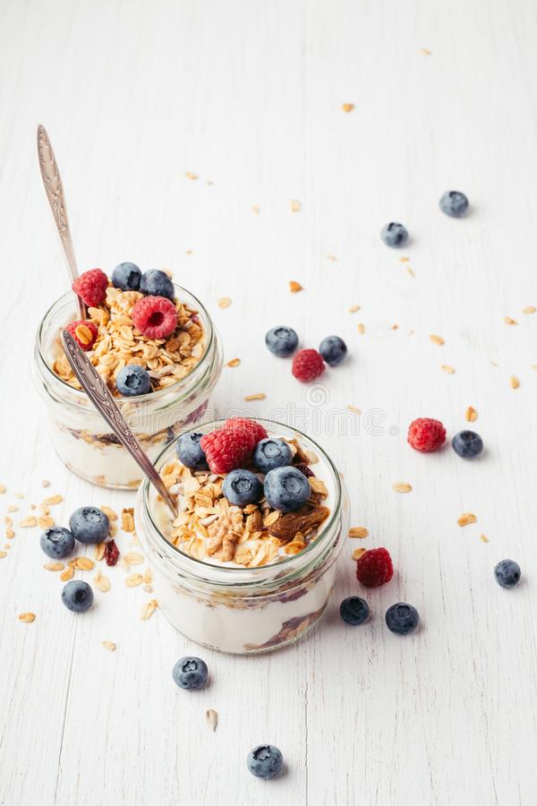 Granola with berries and yogurt in jars. stock photography
