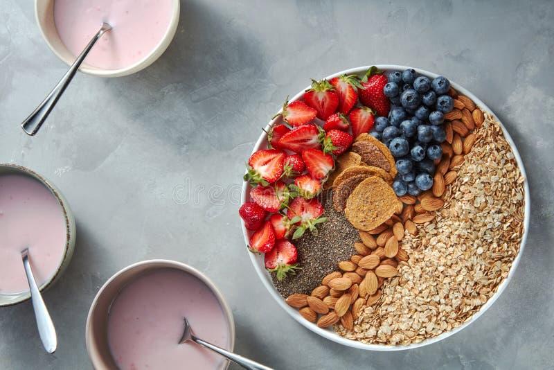 Granola, bessen, noten, chia en yoghurt in een plaat op een grijze concrete achtergrond Ingrediënten voor ontbijt Hoogste mening royalty-vrije stock foto
