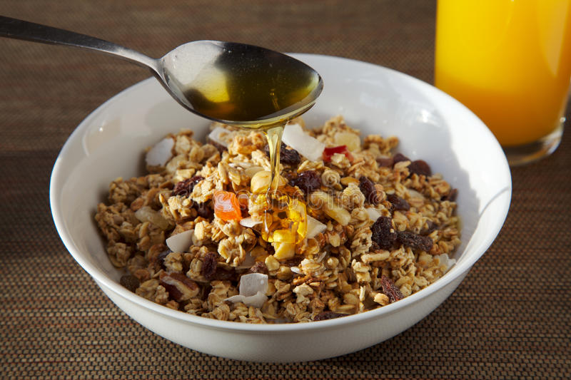 Granola Breakfast Bowl. Granola in a breakfast bowl with orange juice and spoon dripping with honey stock photo