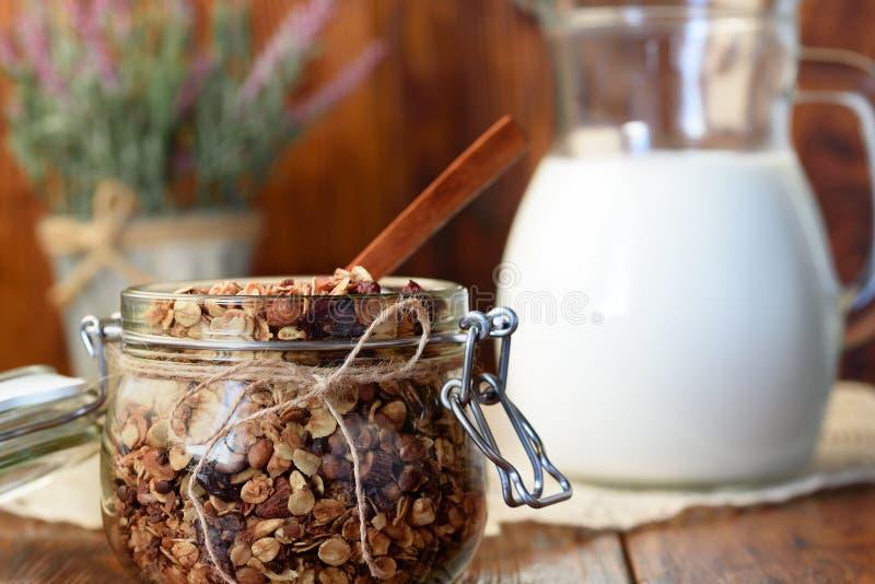 Granola caseiro com porcas, arandos e abricós secados, e um jarro de leite Foco seletivo, espaço da cópia fotos de stock