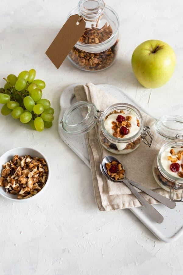 Granola caseiro com porcas, frutos e iogurte em uns frascos no fundo branco Alimento saud?vel, frutos, fazendo dieta Tempo de caf imagens de stock