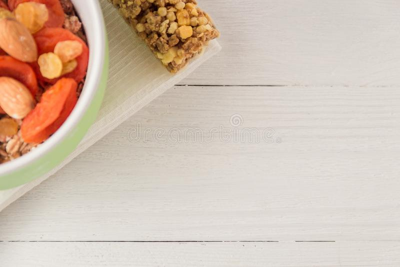 Granola cereal flakes with dried fruit, nuts in green bowl on white wooden table. Top view with copyspace. stock image