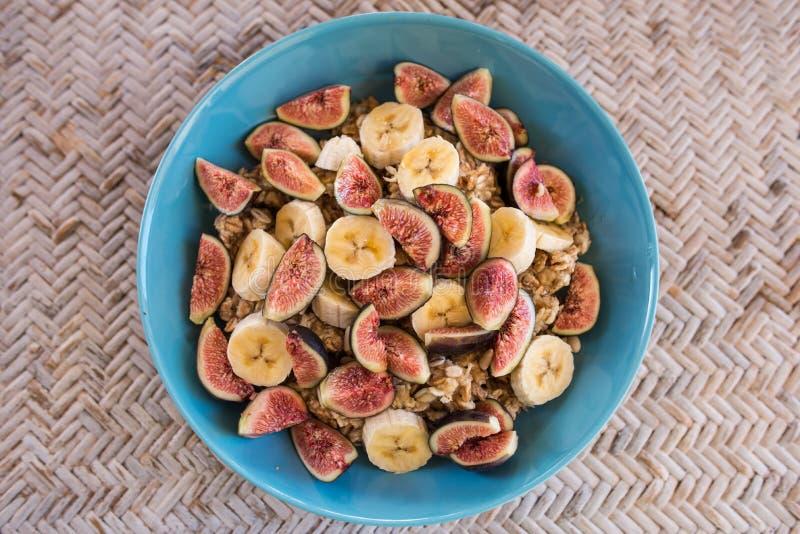 Granola com bananas, figos e mel, bacia azul imagem de stock royalty free