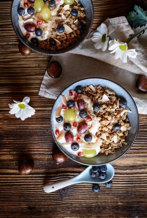 Granola com iogurte, uvas, mirtilos, microplaquetas do coco e puré de castanha fotografia de stock