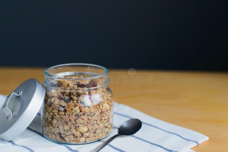 Granola com os flocos dos amendoins, das avelã, da aveia e do trigo no frasco de vidro fotos de stock royalty free