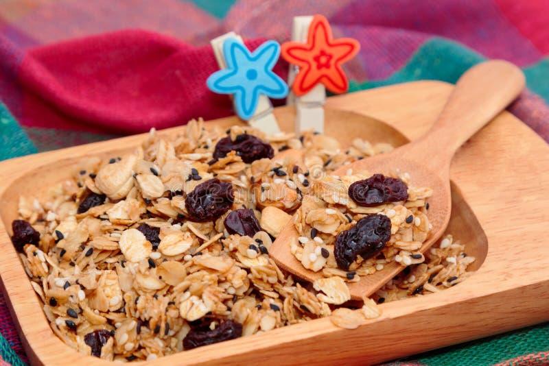 Granola con i dadi ed i semi in piatto di legno per sano fotografie stock libere da diritti