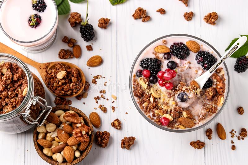 Granola crispy honey muesli with natural yogurt, fresh berries, chocolate and nuts in a bowl against a light background, healthy royalty free stock photos