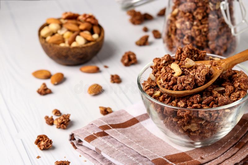 Granola crispy muesli with natural honey, chocolate and nuts in a glass bowl against a white background, healthy food, horizontal. Granola crispy muesli with royalty free stock photos
