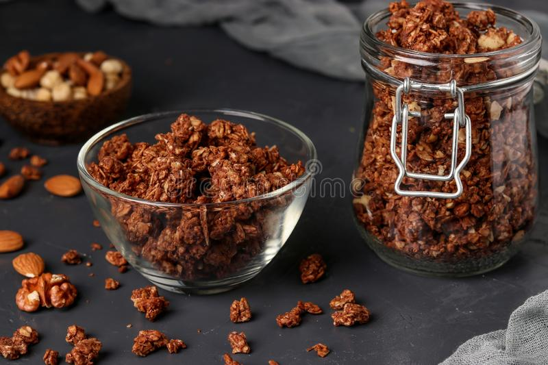 Granola crispy muesli with natural honey, chocolate and nuts in a glass jar and bowl against a dark background, healthy food, royalty free stock photo