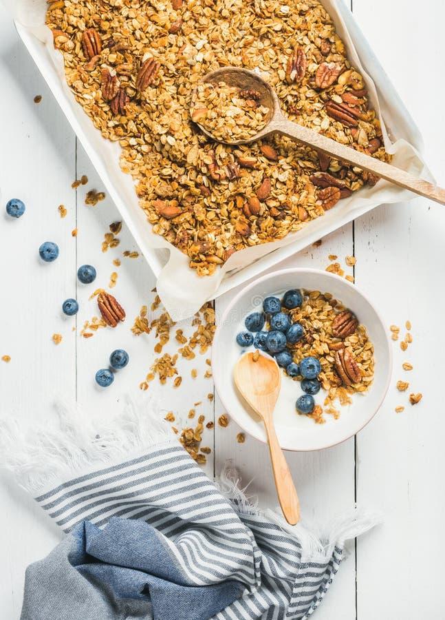 Granola d'avoine avec les noix de pécan, le yaourt et la myrtille dans la cuvette photos libres de droits
