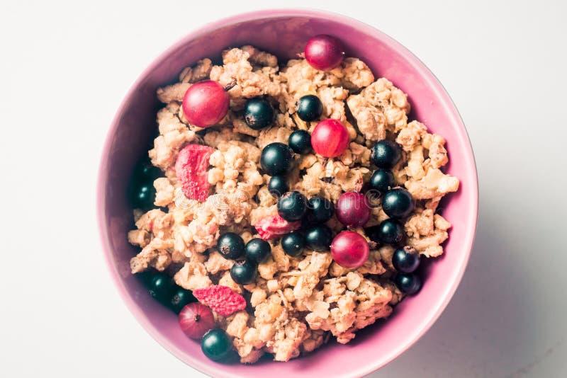 Granola of de vlokken met bessen van zwarte bes en kruisbes in een roze plateren op een witte achtergrond Hoogste mening Gezond stock foto's